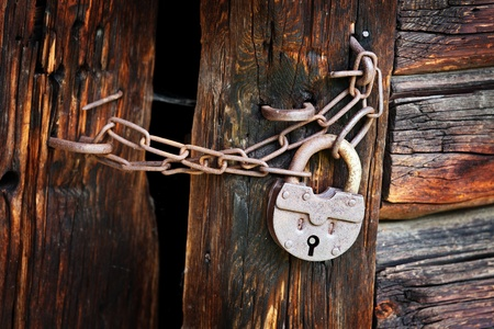 Old rusty padlock and chain on the rural wooden gate photo