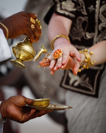connectedness: The ritual watering connectedness fingers newlyweds. Wedding in Sri Lanka