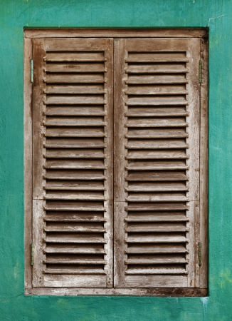 Old vintage window with wooden lattice on green wall photo