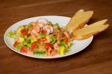 Salad with vegetables, shrimp and sauce photo