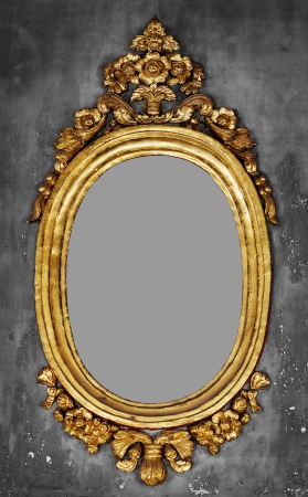 Old-fashioned oval gilt frame for a mirror on a gray concrete wall photo