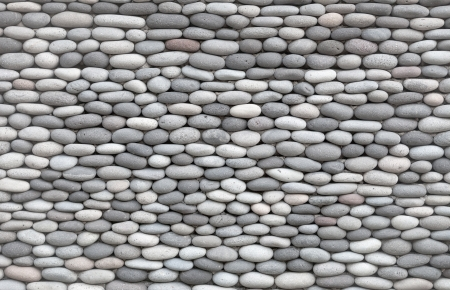 peddle: Background - a wall decorated with smooth round stones Stock Photo