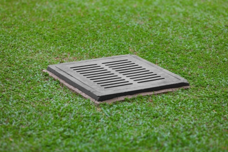 The sewer grate on the lawn - drainage for heavy rain photo