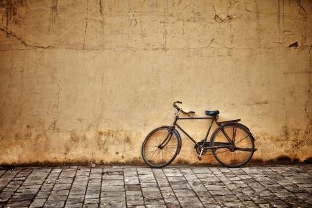 Oude roestige uitstekende fiets in de buurt van de betonnen muur