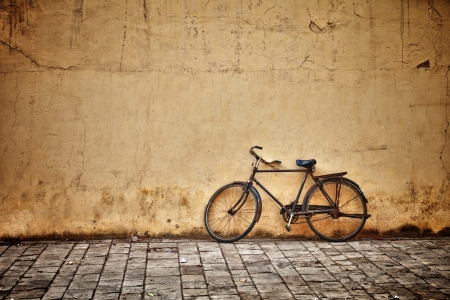 Old rusty vintage bicycle near the concrete wall