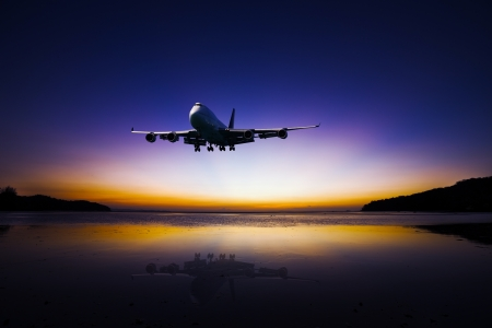 Airplane flying on tropical colorful evening sky over the sea at beautiful sunset with reflection