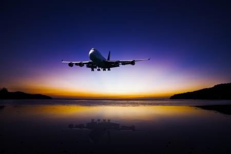 Avion volant sur le ciel du soir tropical coloré sur la mer au beau coucher de soleil avec la réflexion