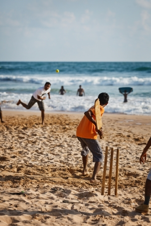 BENTOTA, SRI LANKA - APR 28: Teenagers play cricket with bat and ball on sandy beach on Apr 28, 2013 in Bentota, Sri Lanka. Cricket is the most popular game in Sri Lanka.