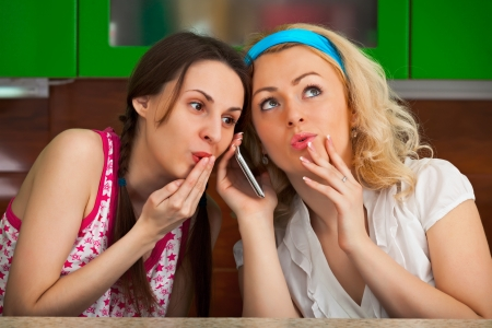 Two funny girlfriend get a phone call in the kitchen photo