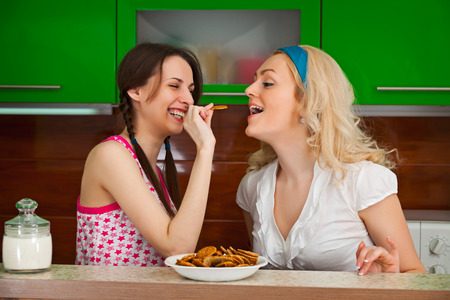 Two young girlfriends funny testing the cookies in the kitchen photo