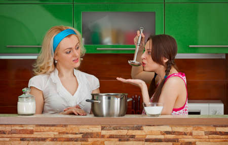 Two girlfriends try to soup on the kitchen photo