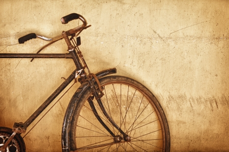 Old-fashioned rusty bicycle near the grunge wall photo