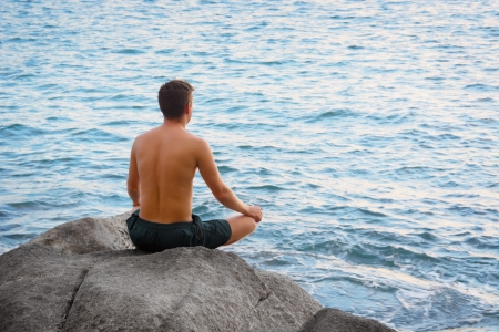 Man sitting in the lotus position and looking at the sea photo