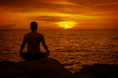Man meditating at sunset. Tropical beach in Thailand photo
