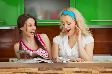 Funny girlfriends browsing magazines in the kitchen photo