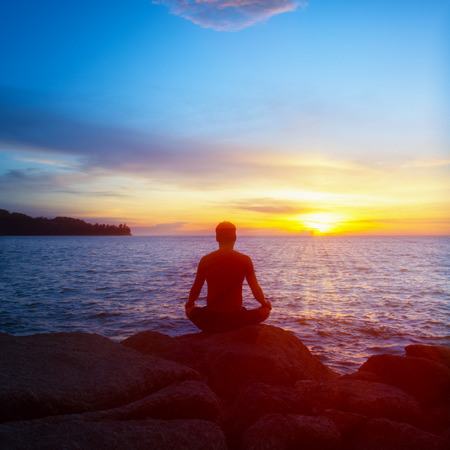 A young man practices yoga on the beach at sunset photo