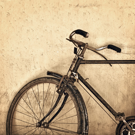 Old rusty bicycle on the grunge wall background