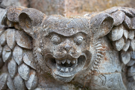 animal ritual: Muzzle fantastic beast on the wall of an old temple in Indonesia
