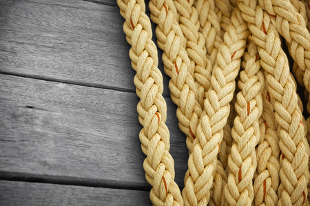 Vintage nautical knots background with copy-space. Big marine sea ropes on wooden desk photo