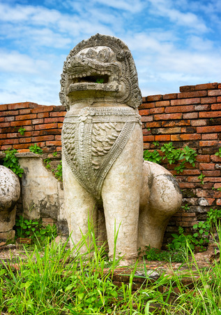 ancient creature: Ruins of ancient temple in Ayutthaya, Thailand. Stone statue of a lion-like creature Stock Photo