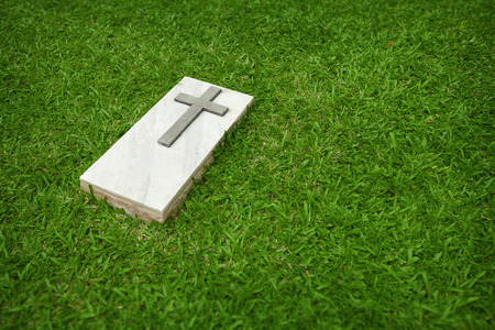 Marble tombstone with the simple Christian cross on a green lawn photo