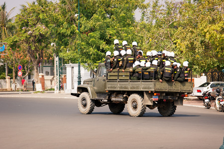 security vest: PHNOM PENH, CAMBODIA - 29 DEC 2013: Cambodian riot police moved by truck