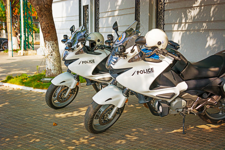 a white police motorcycle: PHNOM PENH, CAMBODIA - 29 DEC 2013: Cambodian police modern motorcycles parked on the sidewalk