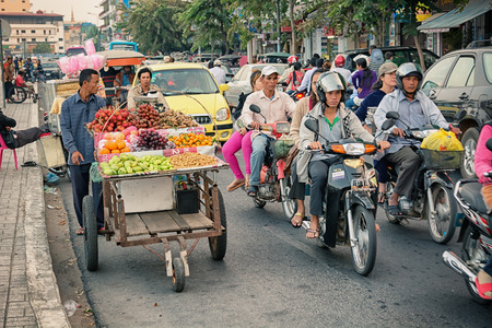 penh: PHNOM PENH, CAMBODIA - 29 DEC 2013: Heavy traffic through the city streets in the evening. The main part of transport - motorcycles Editorial