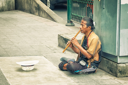 earns: BANGKOK, THAILAND - 21 NOV 2013: Poor man earns his living with music on the street Editorial