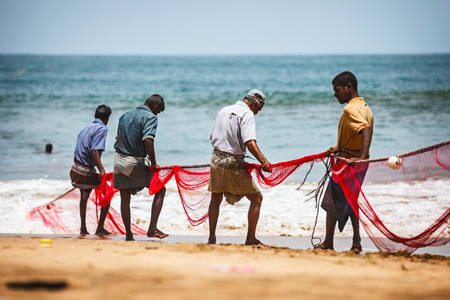 BENTOTA, SRI LANKA - 26 APR 2013: Sri Lankan fishermen pull big net in Bentota, Sri Lanka. Fishing is a key occupation on Sri Lanka sea coast.