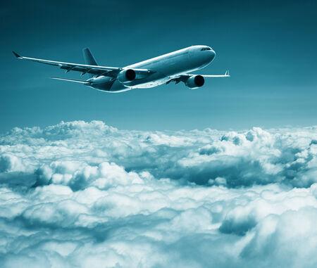 A passenger plane flies over cumulus clouds photo