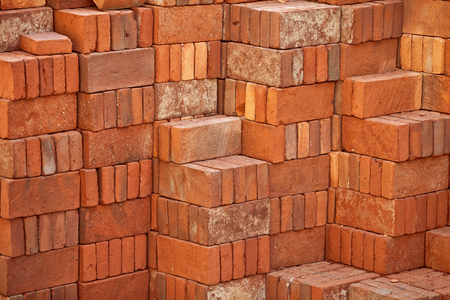 Pile of clay red bricks prepared forbuilding photo