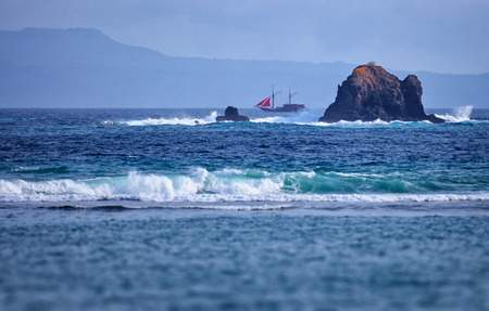 Old two-masted schooner near the rocks in the sea. Indonesia, Bali island photo