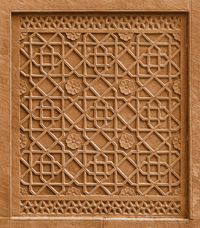 Decorative architectural element with traditional ornament cutting out in stone. India, Agra photo