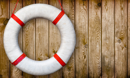 White lifebuoy on a wooden wall
