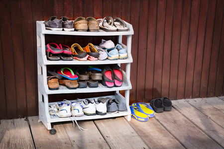 A variety of colorful shoes, neatly ordered on a plastic shoe rack outside a wooden house. Stock Photo