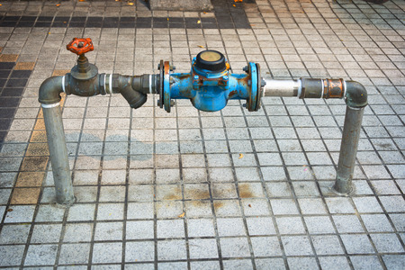 protruding: Water pipes with a meter and main shutoff valve, protruding from the sidewalk along a public street.