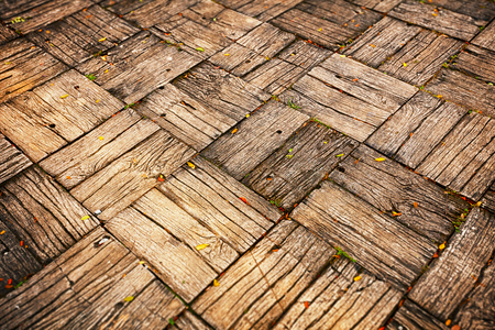 oblique: Background, depicting a weathered, parquet style wooden deck with alternating directions of woodgrain. Stock Photo