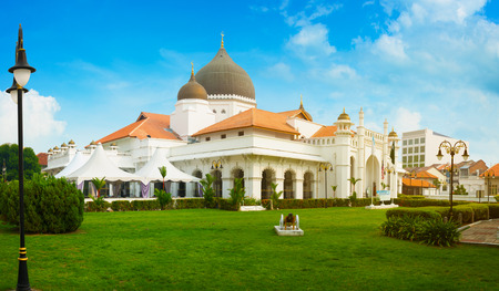 Beautiful architecture and domes of the Kapitan Keling Mosque in Georgetown, Penang, Malaysia, standing against a bright blue sky. Stock Photo