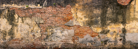 Very old wall in historic Georgetown, Penang, Malaysia, with crumbling facia revealing the underlying brickwork in several places. Stock Photo