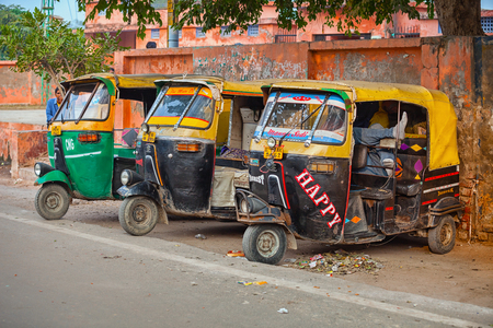 motorizado: AGRA, INDIA - CIRCA 11 2012: Tres, pintadas de colores, rickshaws, estacionado a la sombra en el hombro de una calle típica en Agra, India motorizados.