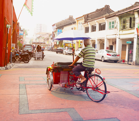 pedals: MALAYSIA, PENANG, GEORGETOWN - CIRCA JUL 2014: A pedicab driver pedals his cycle rickshaw, laden with cargo, across the ornate pavement of an intersection in Georgetown.
