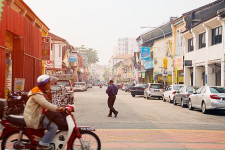 paso de peatones: Malasia, Penang, GEORGETOWN - CIRCA 07 2014: Un hombre cruza una calle típica en Georgetown como una moto pasa por detrás de él.