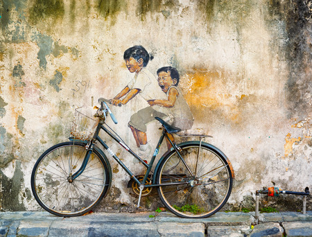 georgetown: GEORGE TOWN, PENANG, MALAYSIA - CIRCA JUL 2014: Public art in Malaysia uses contrasting media of sculpture and painting for this mural of two girls riding a bicycle.