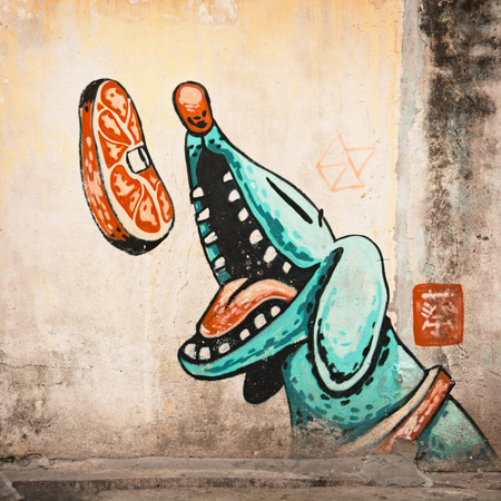MALAYSIA, PENANG, GEORGETOWN - CIRCA JUL 2014: Large mural of a blue, cartoon style dog catching a steak in the air