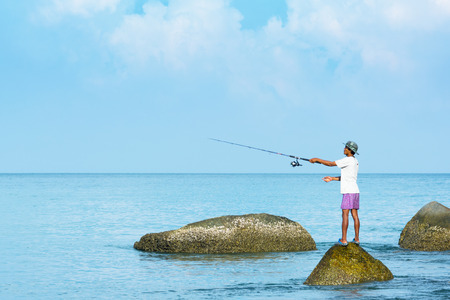 precarious: PHUKET, THAILAND - CIRCA APR 2014: Thai fisherman casts with his rod from a precarious standing position atop a half submerged boulder at low tide.
