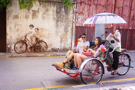 rikscha: Malaysia, Penang, Georgetown - CIRCA Juli 2014: Ein echtes Fahrrad, nebeneinander über eine lebensgroße Wandbild von einem Fahrrad, und Touristen in einer Fahrradrikscha.