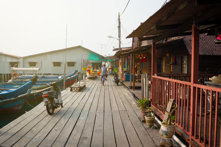 georgetown: MALAYSIA, PENANG, GEORGETOWN - CIRCA JUL 2014: This boardwalk along Chew Jetty serves as the main access for members of the Chew Clan to reach their homes and businesses.