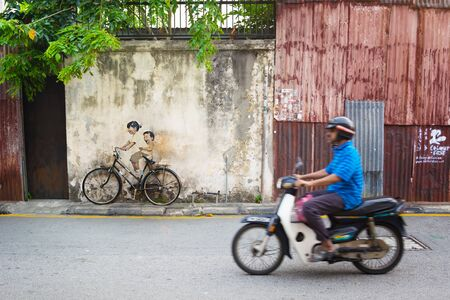 juxtaposition: MALAYSIA, PENANG, GEORGETOWN - CIRCA JUL 2014: Real bicycle juxtaposed over lifesize mural of children riding a bicycle. Editorial