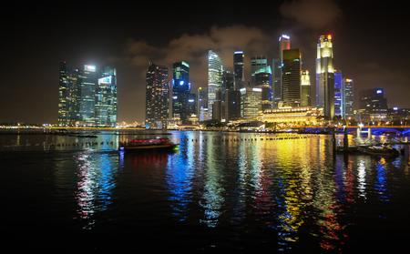 encrespado: Luces intr�pidos y coloridos edificios de la ciudad de gran altura de Singapur, que se refleja en el agua ligeramente agitada del puerto por la noche. Editorial